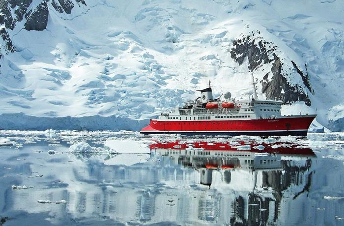 The G Expedition ship sailing past a snowy mountain in Antarctica