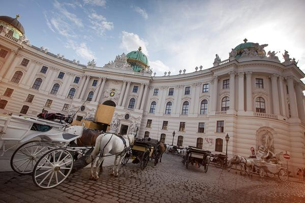 horse-pulled carriages parked outside an elegant chateau