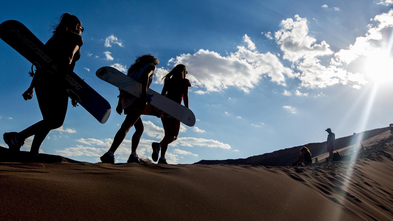 Travellers Sandboarding In The Desert Of Atacama Chile