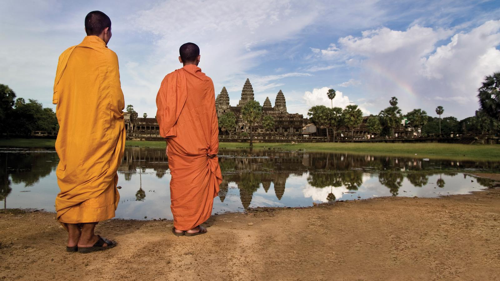 Two monks reflecting over the ancient Angkor Wat temple