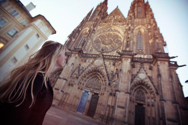 woman gazing up at a gothic cathedral