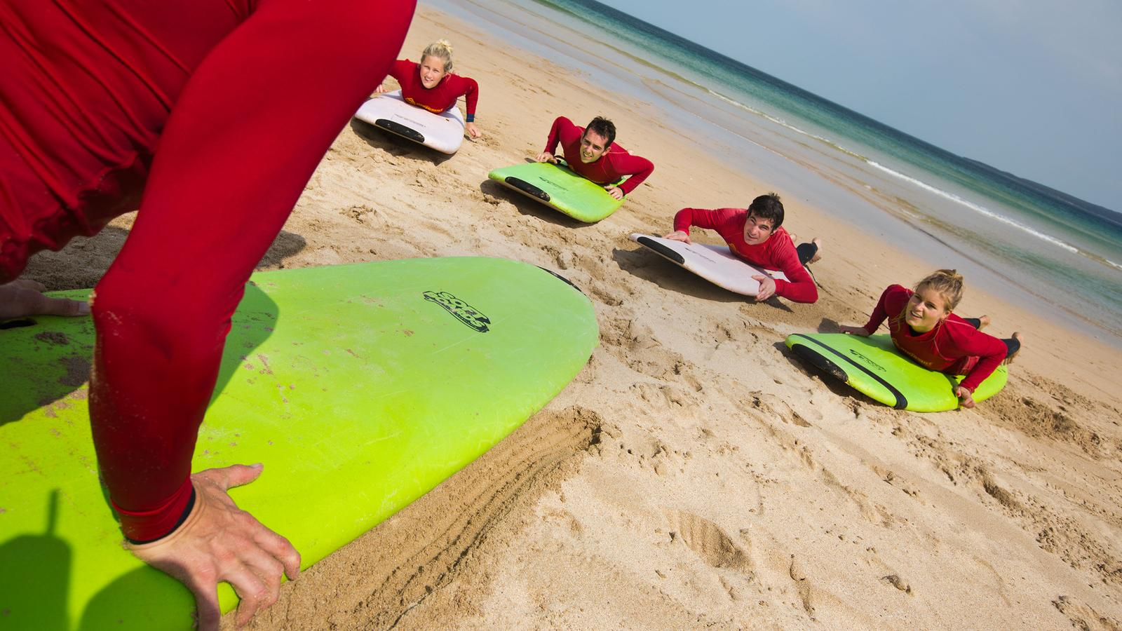 A group of travellers take a surf lesson on a sandy beach in Sydney, Australia