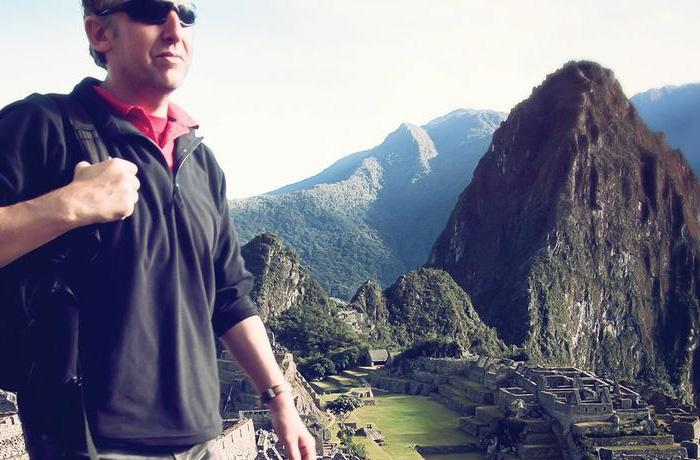 Man in sunglasses walking past Machu Picchu in Peru