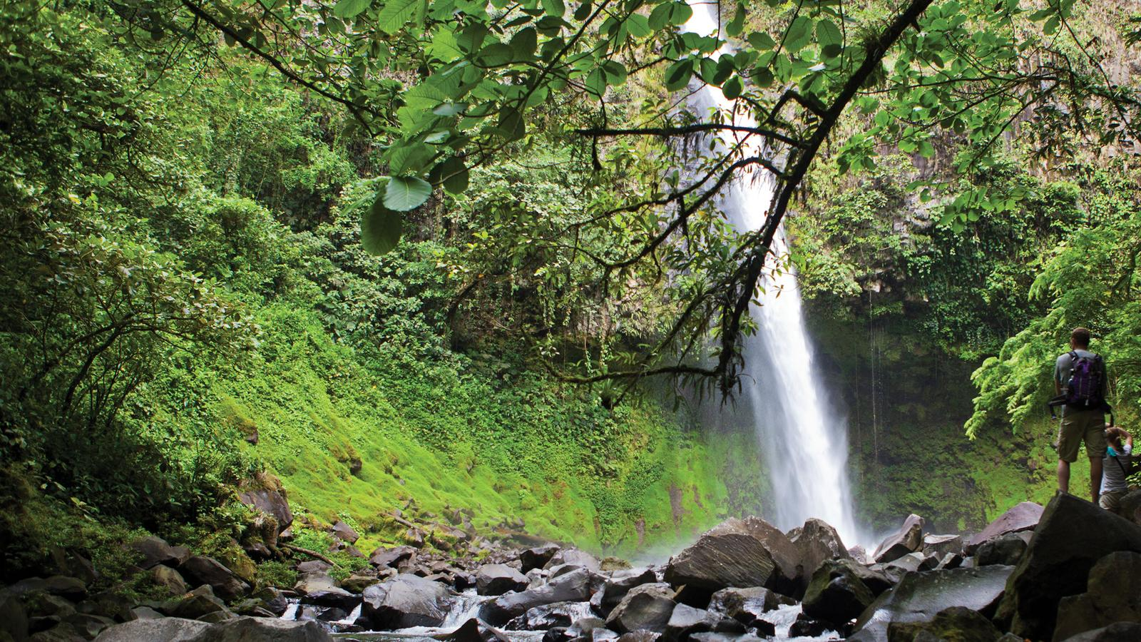 Travellers visiting a waterfall at Arenal National Park in Costa Rica