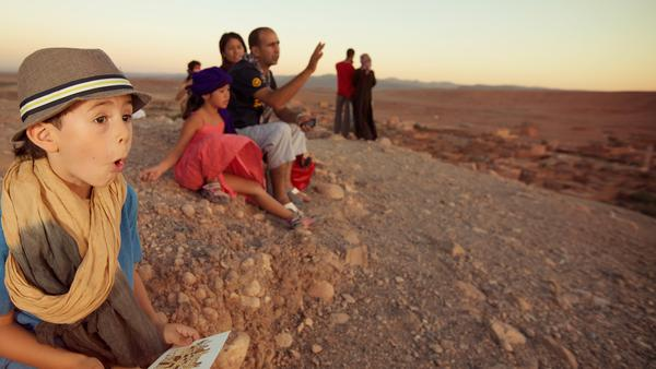 a family seated on a sand dune, marvelling as their CEO tells a story
