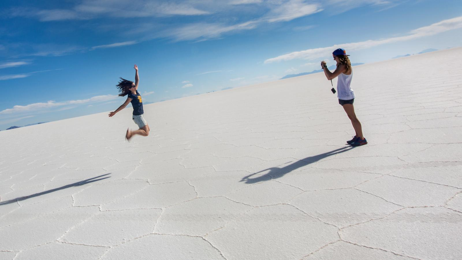 Travellers using the Salt Flats of Bolivia as a backdrop for photos