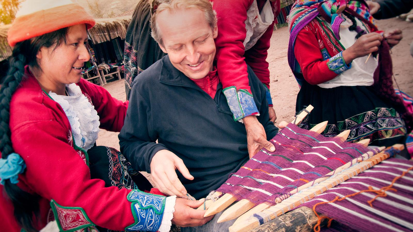 A traveller learning about how traditional weaving works from a local in Peru