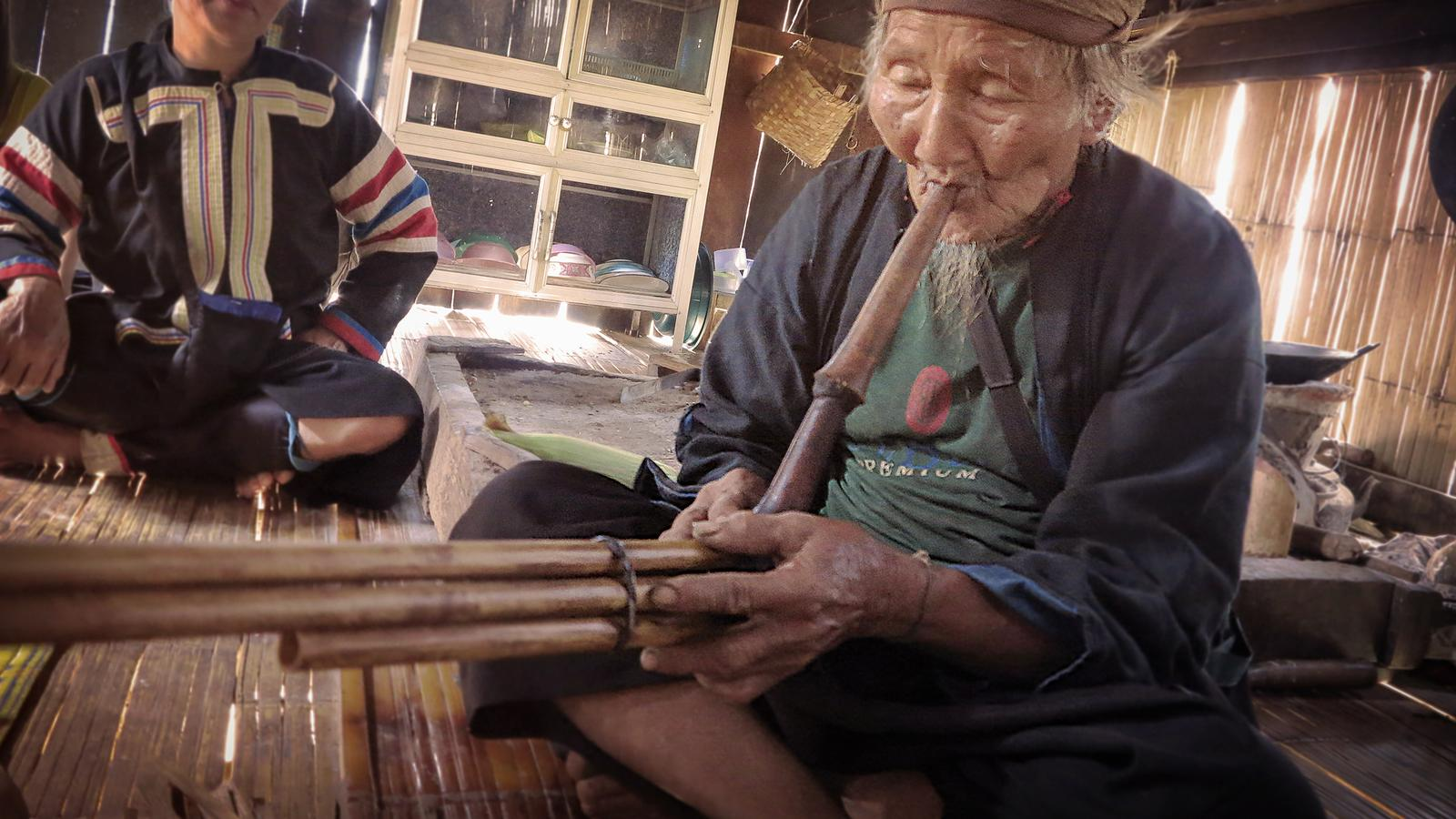 A local plays Lahu music in the hilltribe village of Thailand