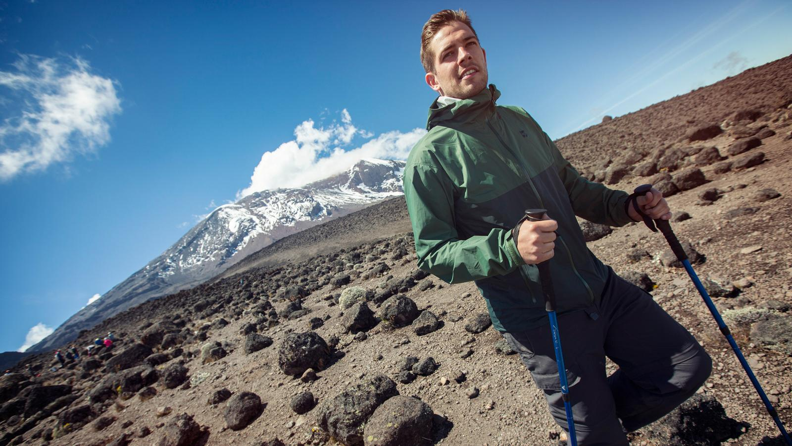 Traveller confidently hiking up the rocky trails of Kilimanjaro in Tanzania