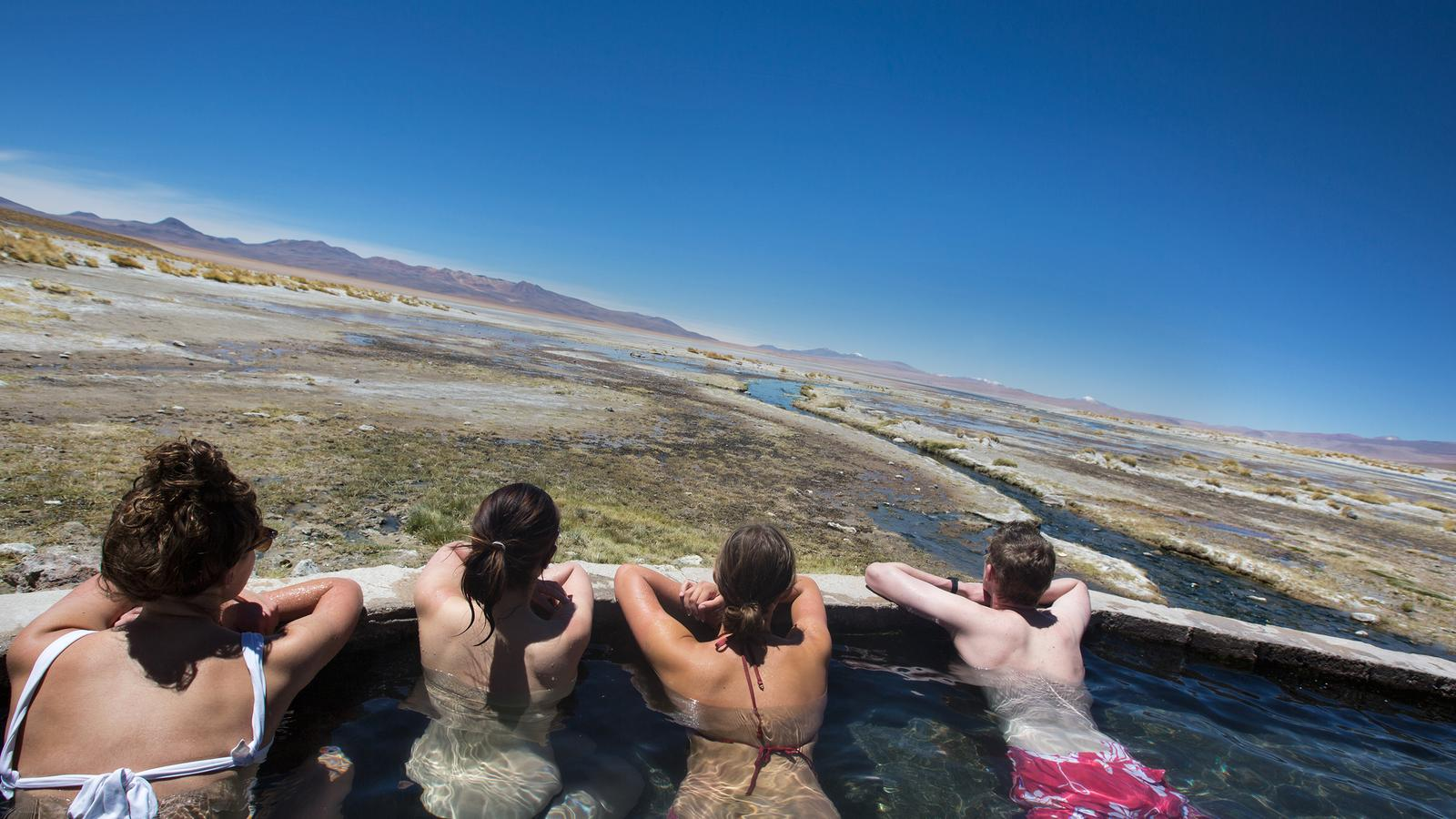 Travellers enjoy the views of Uyuni from the hot springs
