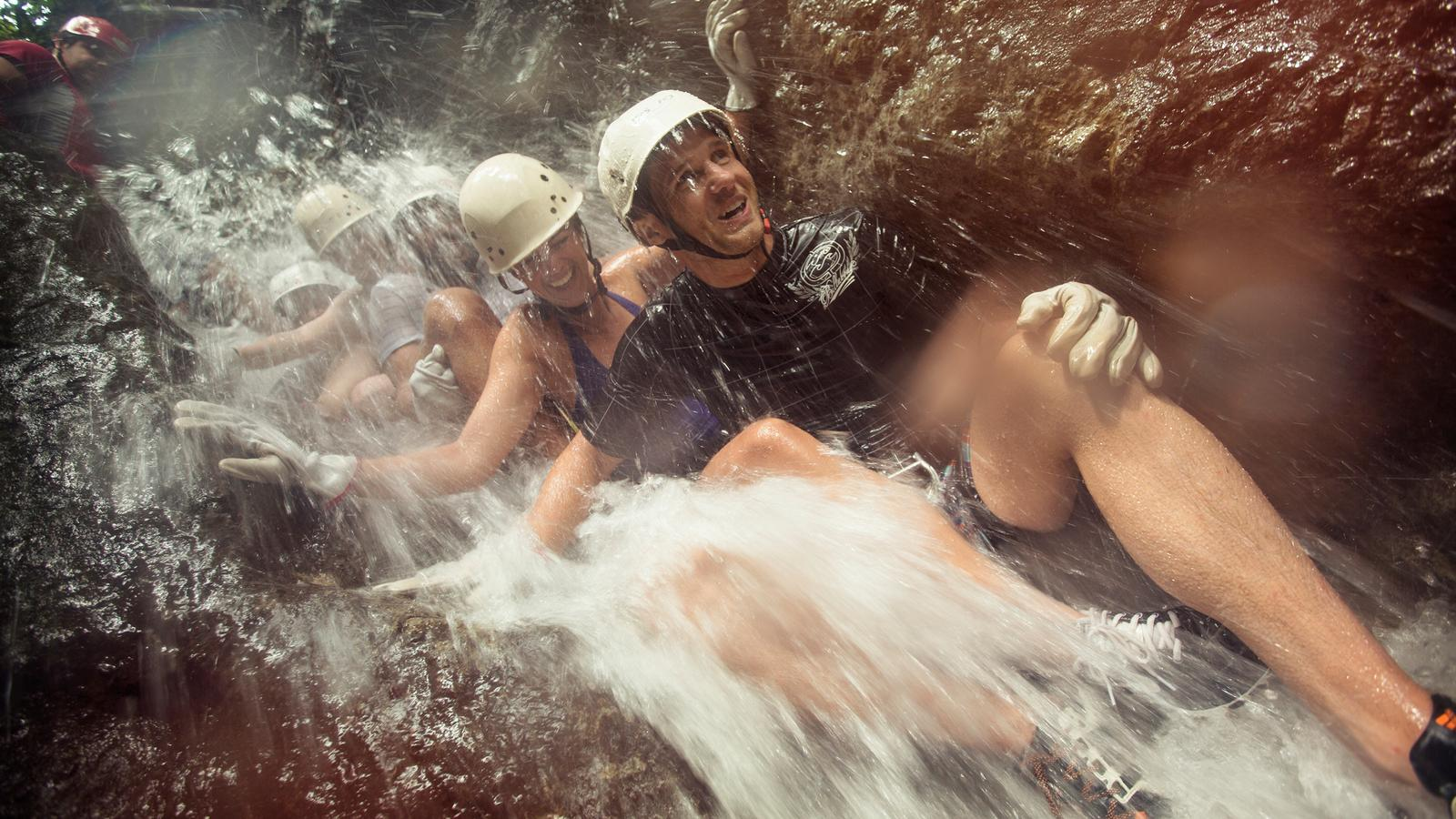 A group of travellers canyoneering down a waterfall in Costa Rica