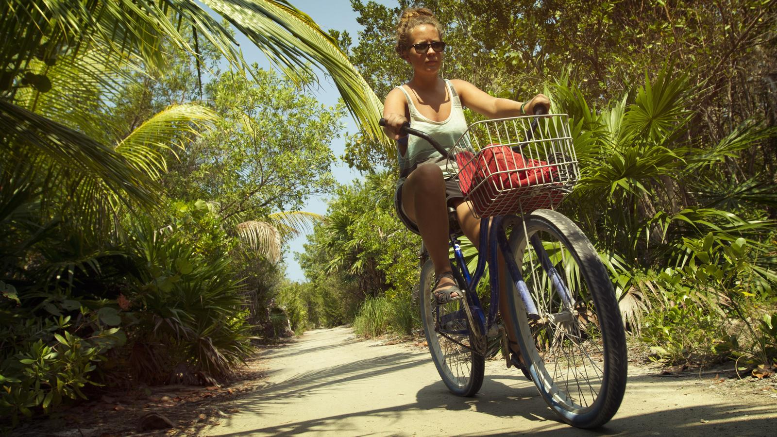 Female traveller biking down a path amongst beautiful lush scenery in Central America
