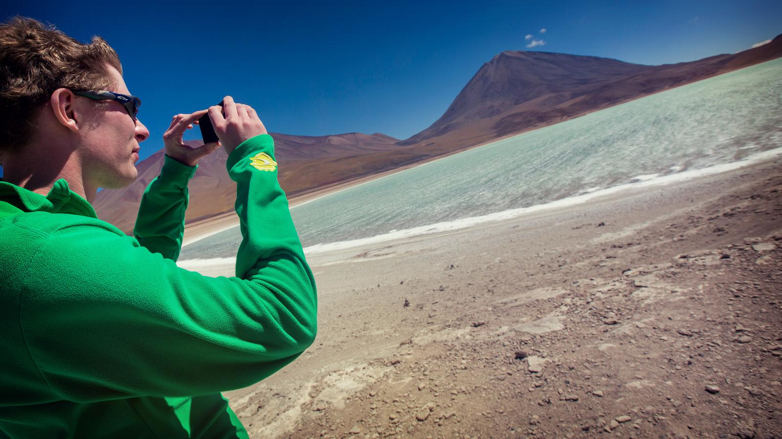 A traveller taking photos of the Uyuni green lagoon during a beautiful clear day in Bolivia