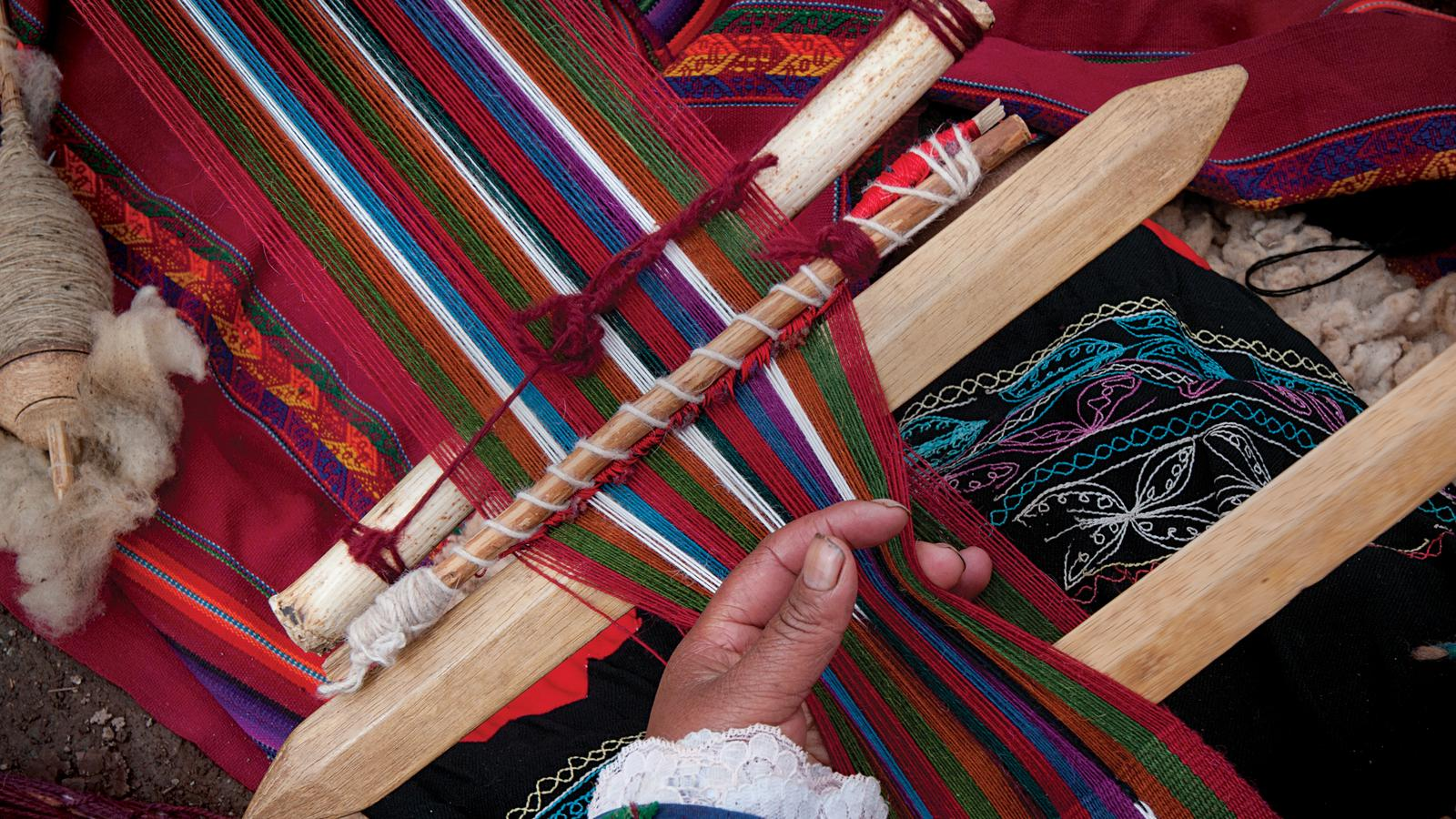 Close up photo of a local women weaving traditional garments at the Womens Weaving Coop in Peru