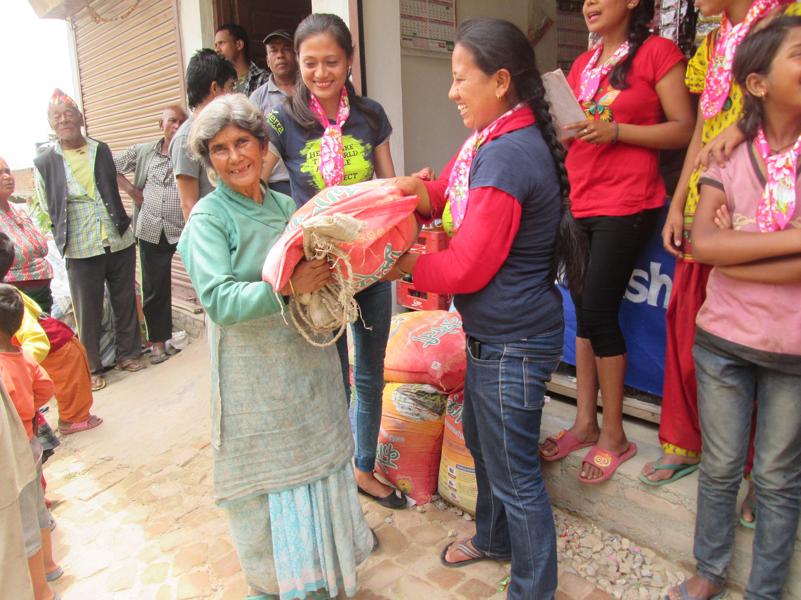 Indira and Manisha from Sisterhood of Survivors handing out bags of rice in Nuwakot just two weeks after the earthquake.