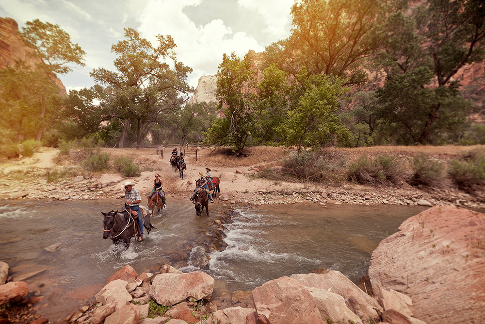 Crossing a river on horseback in Zion Canyon, Utah.