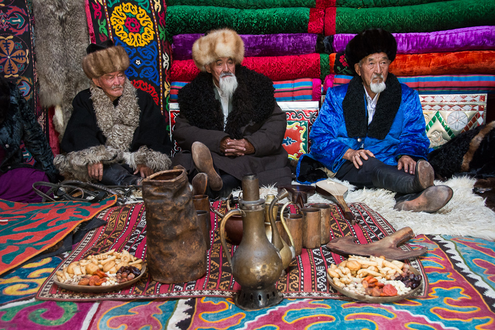 """Kyrgyz elder men wait for guests in a yurt. Notice the colorful """"shyrdak"""" carpets on the ground."""