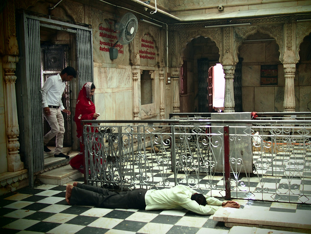 Paying respects to Karni Mata, including prostrating on the floor.