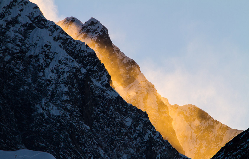 The morning sun catching its light in a spindrift off the side of this Himalayan peak.