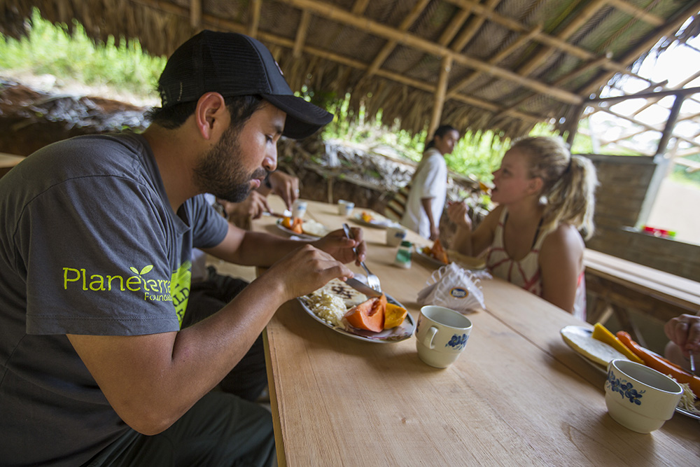 Travellers enjoy a meal with the Wiwa people.