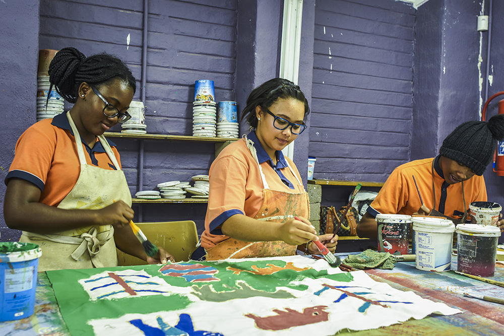 G Adventures travellers participate in a painting workshop at the Khwa ttu San Cultural Centre.