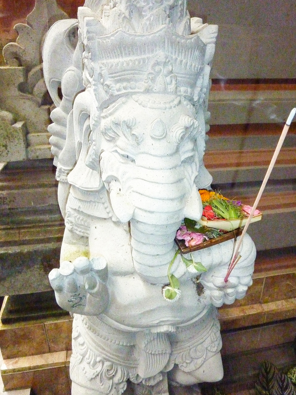 A canang sari offering tucked into a Ganesh statue.
