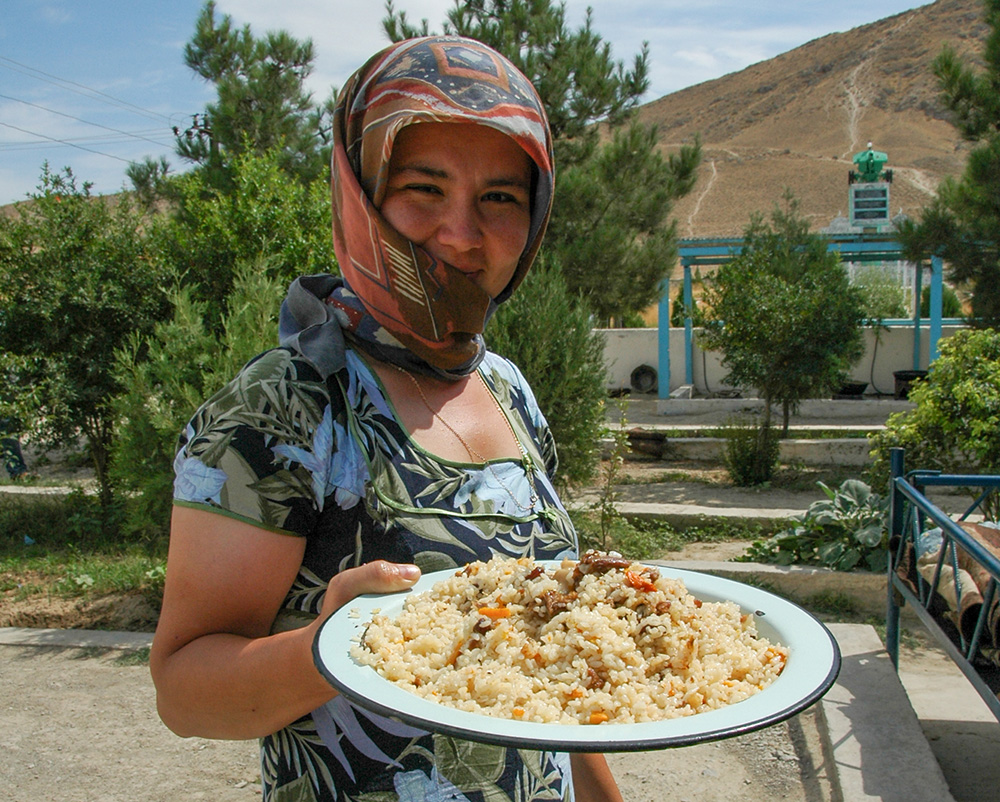 A young woman offers us a plate of plov for lunch at a local pilgrimage site.